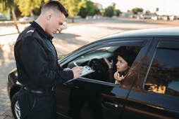 Picture of a Male police officers checking vehicle driver and giving a ticket because driving under the influence of alcohol on the road